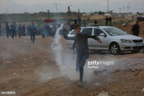 A Palestinian protester throws back an Israeli teargas canister during clashes between Israeli troops and Palestinian protesters near the border...