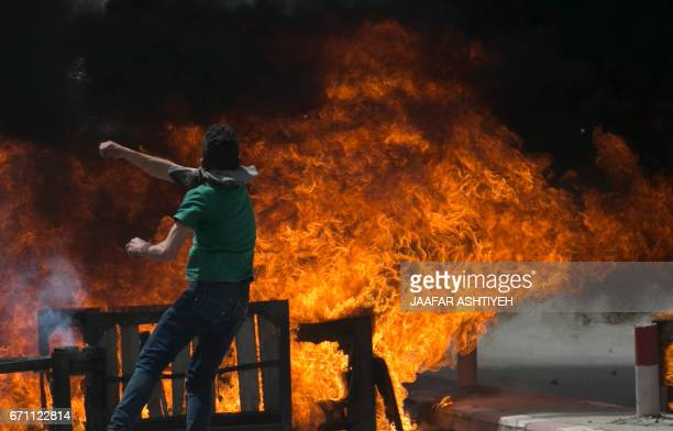Palestinian protester throws rocks towards Israeli forces during clashes in the West Bank village of Beita southeast of Nablus city after a protest...