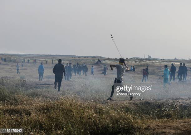 "Palestinian protester throws stone with a slingshot to Israeli forces during a protest within the ""Great March of Return"" at Israel-Gaza border, in..."
