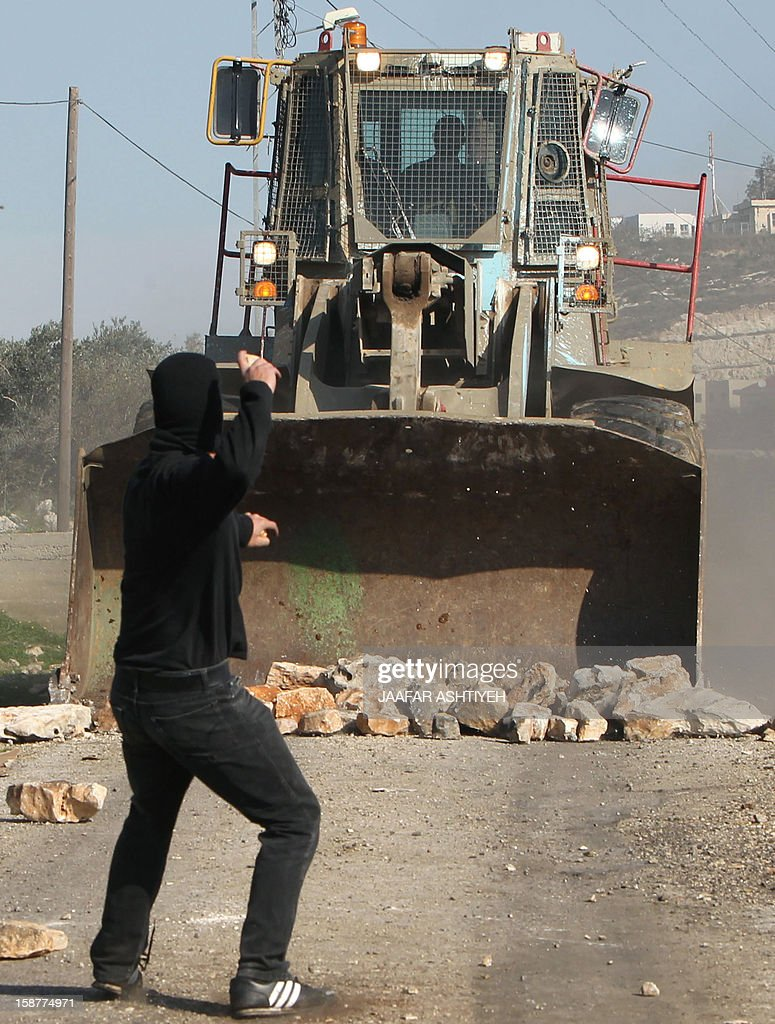 A Palestinian protester throws stones towards an Israeli maned bulldozer during clashes following a demonstration against the expropriation of Palestinian land by Israel in the village of Kfar Qaddum, near the occupied West Bank city of Nablus, on December 28, 2012.