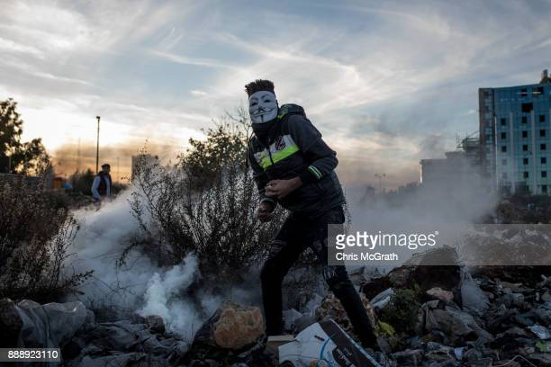 Palestinian protester tries to pickup a tear gas cannister to throw back at Israeli border guards during clashes near an Israeli checkpoint on...