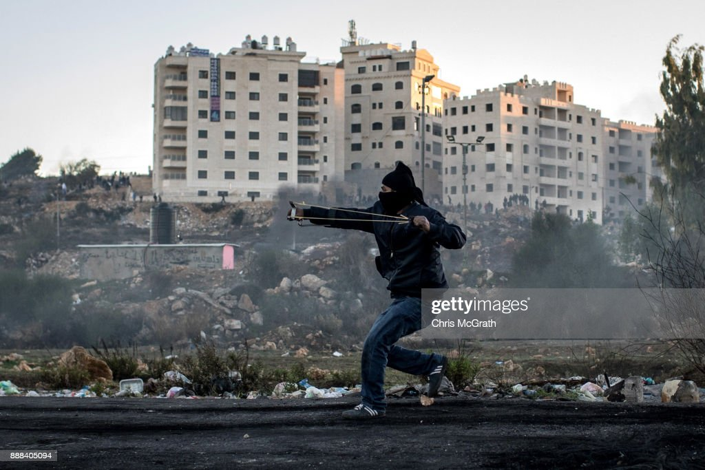 A Palestinian protester uses a sling shot to hurl rocks during clashes with Israeli border guards near an Israeli checkpoint on December 8, 2017 in Ramallah, West Bank. At least 50 Palestinians have been wounded in clashes between Palestinian protestors and Israeli security forces in the West Bank and the Gaza Strip on Friday after thousands of protestors took to the streets in a second 'Day of Rage' following U.S. President Donald Trump's decision to recognize Jerusalem as Israel's capital on Wednesday.