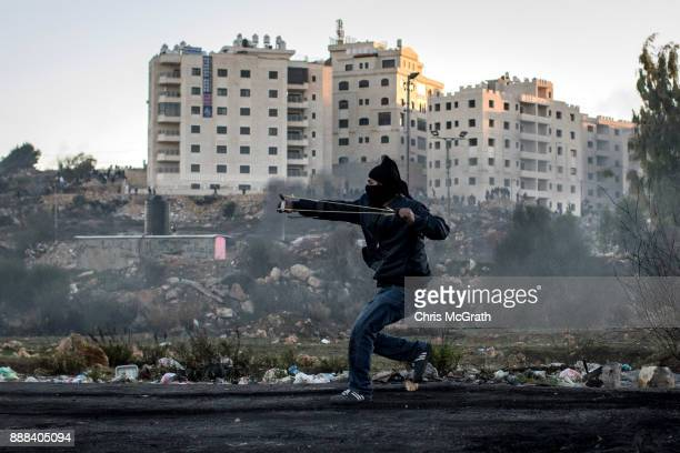 Palestinian protester uses a sling shot to hurl rocks during clashes with Israeli border guards near an Israeli checkpoint on December 8 2017 in...
