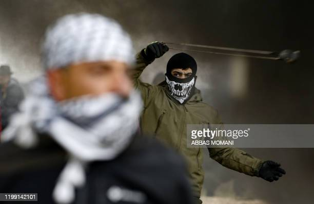 Palestinian protester uses a slingshot during a demonstration against a USbrokered peace proposal in the occupied West Bank village of Bilin near...