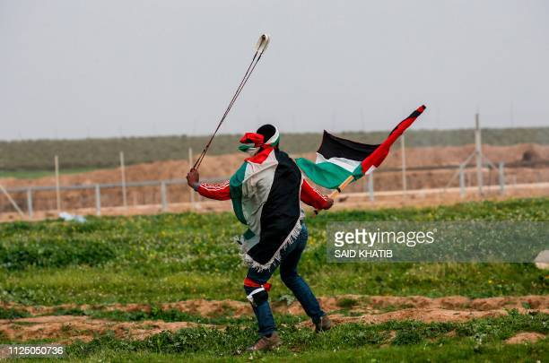 A Palestinian protester uses a slingshot during clashes with Israeli forces during clashes with Israeli forces following a demonstration near the...