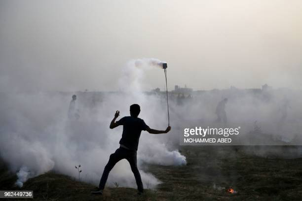 Palestinian protester uses a slingshot in the smoke billowing from tear gas shot by Isreali forces during a demonstration along the border between...