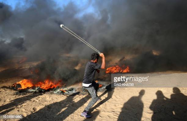 Palestinian protester uses a slingshot next to burning tyres during a demonstration at the IsraelGaza border east of Khan Yunis in the southern Gaza...