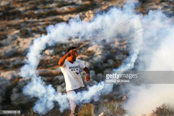 Palestinian protester uses a slingshot to hurl back a tear gas canister towards Israeli security forces during clashes in the village of Ras Karkar...