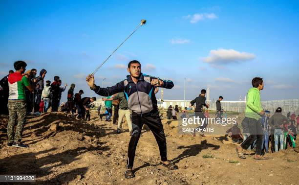 Palestinian protester uses a slingshot to hurl objects during clashes with Israeli forces across the fence following a demonstration by the border...