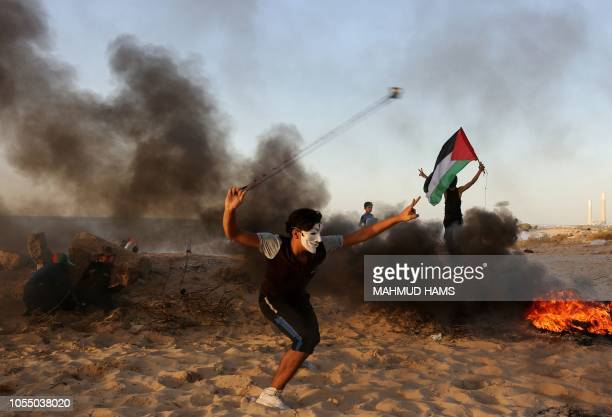 Palestinian protester uses a slingshot to hurl stones during a demonstration on the beach near the maritime border with Israel in Beit Lahia in the...