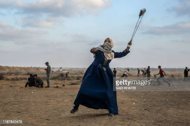 Palestinian protester uses a slingshot to hurl stones during clashes with Israeli forces across the barbedwire fence following a demonstration along...
