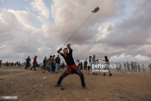 Palestinian protester uses a slingshot to hurl stones during the clashes Palestinians clashes with Israeli security forces demanding for an end to...