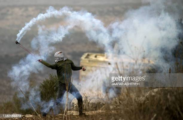 Palestinian protester uses a slingshot to return a tear gas canister fired by Israeli forces amid clashes following a weekly demonstration against...
