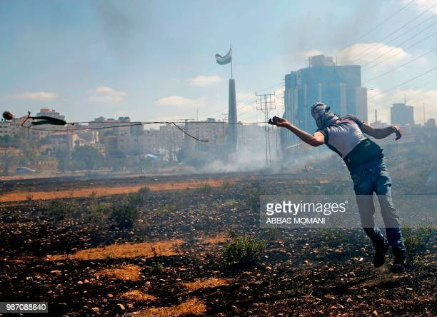 Palestinian protester uses a slingshot to throw a rock on Israeli forces during a demonstration near the Jewish settlement of Beit El near Ramallah...