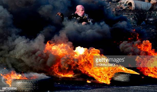 Palestinian protester uses a slingshot to throw a stone through the smoke of burning tires during clashes with Israeli forces in the West Bank city...