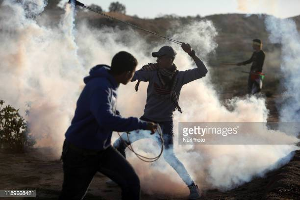 Palestinian protester uses a slingshot to throw back a tear gas canister at Israeli forces amidst clashes during a demonstration along the border...