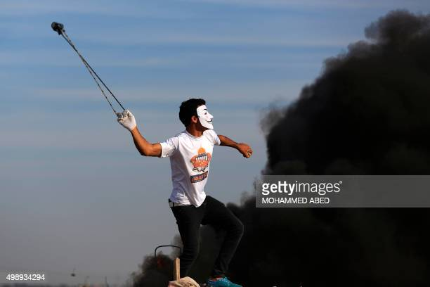 A Palestinian protester uses a slingshot to throw stones at Israeli security forces during clashes along the border with Israel on the eastern...