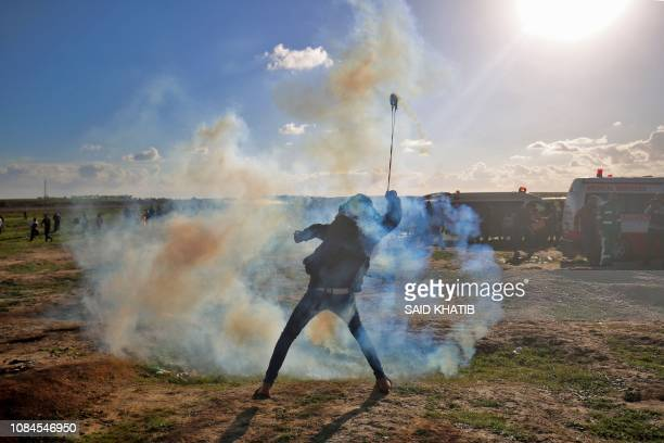 Palestinian protester uses a slingshot to throw tear gas towards Israeli forces during a demonstration along the Israeli fence east of Gaza City on...