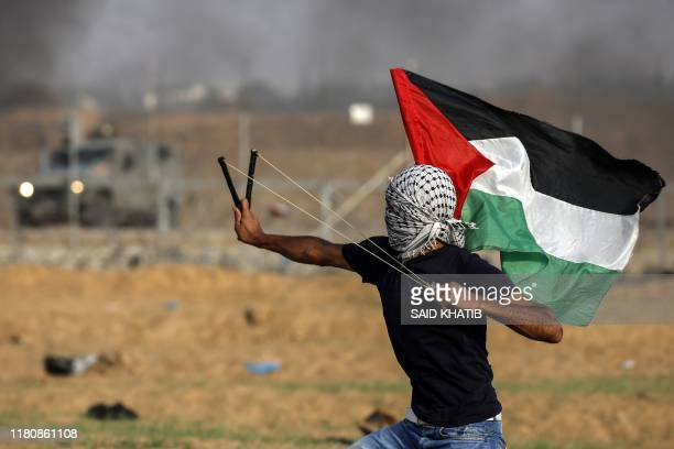 Palestinian protester uses a slinshot to hurl stones toward Israeli troops during clashes following a demonstration along the border fence east of...