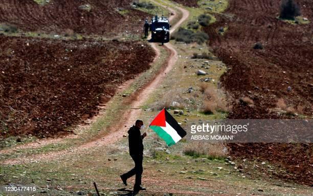 Palestinian protester walks across Israeli forces during a demonstration against Israeli settlements in the village of Deir Jarir near Ramallah in...