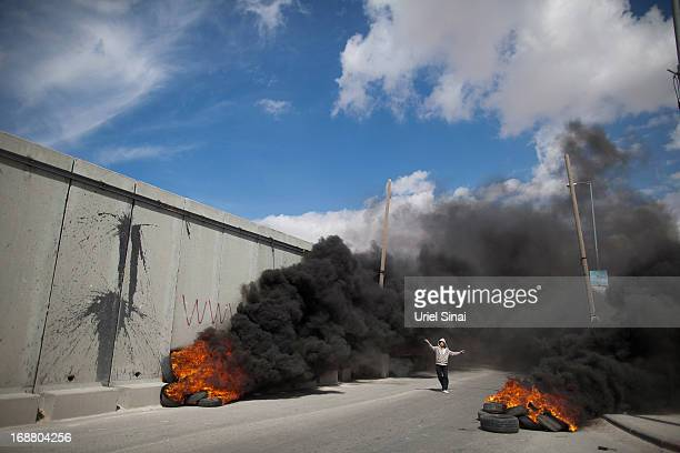 Palestinian protester walks between burning tires during clashes with the Israeli army during Nakba day on May 15 2013 near the Qalandia checkpoint...