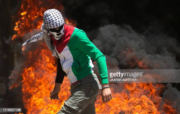 Palestinian protester walks near burning tires during clashes with Israeli forces during a demonstration in the village of Kfar Qaddum in the...