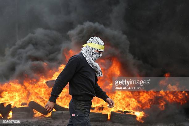 Palestinian protester walks past burning tyres during clashes with Israeli security forces following a demonstration against the expropriation of...