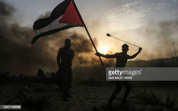 A Palestinian protester waves a national flag as he throws a stone during a demonstration on the beach near the maritime border with Israel in the...