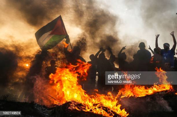 Palestinian protester waves a national flag during a demonstration on the beach near the maritime border with Israel in the northern Gaza Strip on...