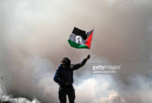 Palestinian protester waves a Palestinian flag amid smoke from tear gas fired by Israeli security forces during a demonstration against the expansion...