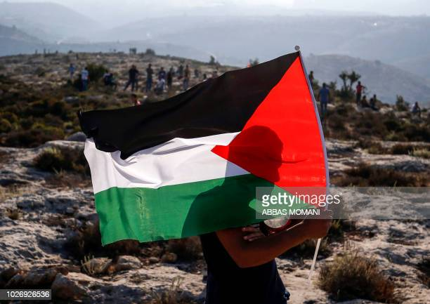 Palestinian protester waves a Palestinian flag during a demonstration in the village of Ras Karkar west of Ramallah in the occupied West Bank on...