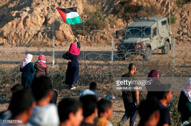 Palestinian protester waves her national flag in front of an Israeli military vehicle during a demonstration along the border with Israel east of...
