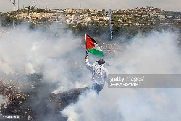 A Palestinian protester wearing a gas mask raises his national flag while standing amidst tear gas smoke fired by Israeli troop during clashes...