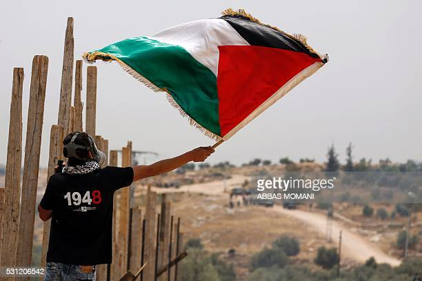 A Palestinian protester wearing a gas mask waves a Palestinian flag in front of Israeli security forces on May 13 2016 in the West Bank village of...