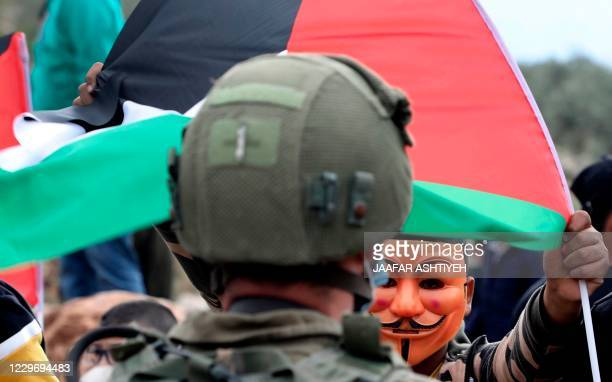 A Palestinian protester wearing a Guy Fawkes mask lifts a national flag during clashes with Israeli security forces following a demonstration against...