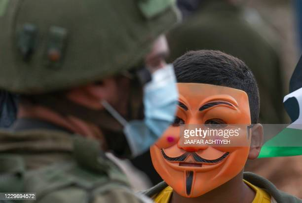 A Palestinian protester wearing a Guy Fawkes mask looks at a member of Israeli security forces amid clashes following a demonstration against the...