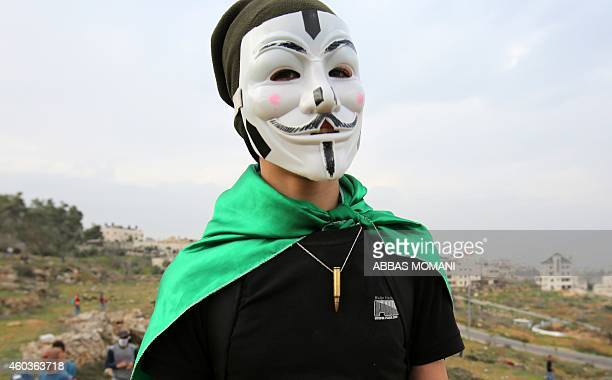 A Palestinian protester wears a Guy Fawkes mask used by the anonymous movement during clashes with Israeli soldiers in the West Bank village of...