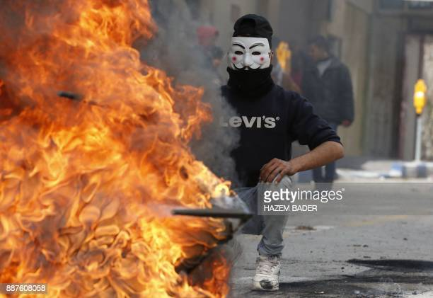 A Palestinian protester wears a Guy Fawkes mask used by the anonymous movement during clashes with Israeli troops on December 7 2017 in Hebron in the...