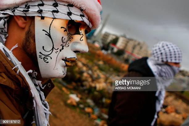 Palestinian protester wears a mask during clashes with Israeli forces on the outskirts of the West Bank city of Ramallah near the Jewish settlement...