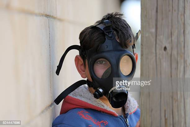 Palestinian protester wears gas mask and watching Israeli soldiers during clashes with Israeli soldiers over the Jewish settlement of Qadomem at Kofr...