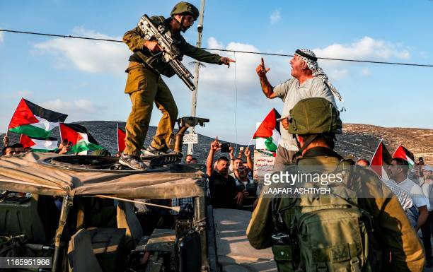 Palestinian protester yells at an Israeli soldier as he confronts him atop an Israeli army vehicle during a protest against Israeli forces conducting...
