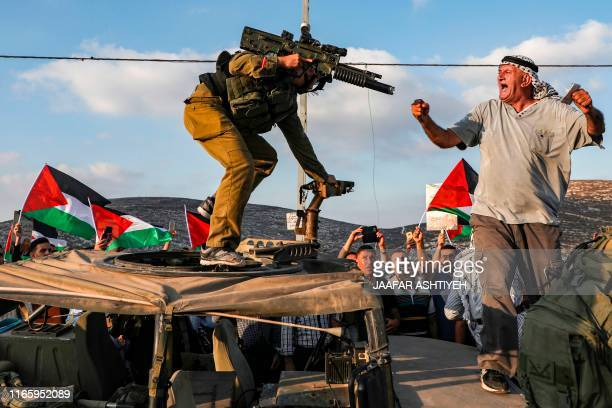 A Palestinian protester yells at an Israeli soldier as he confronts him atop an Israeli army vehicle during a protest against Israeli forces...