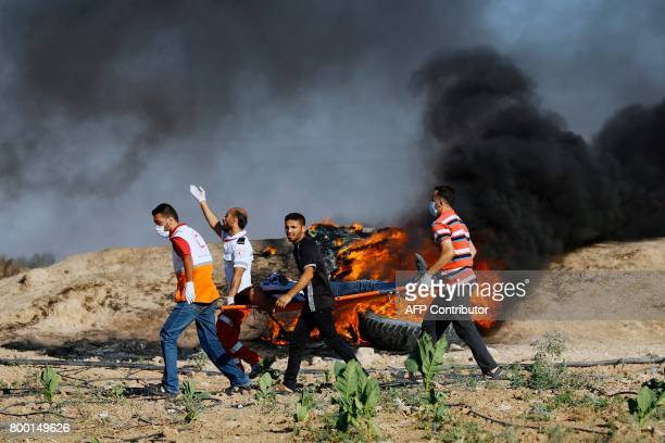 TOPSHOT Palestinian protesters and medics carry a wounded man during clashes with Israeli security forces near the border fence east of Jabalia...
