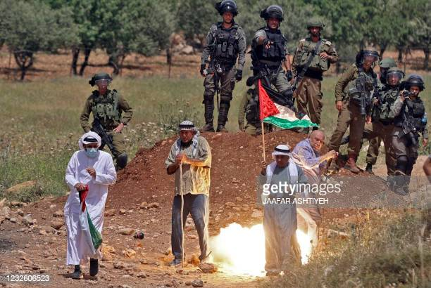 Palestinian protesters are hit by tear gas fired by Israeli security forces during a demonstration against the establishment of Israeli outposts on...