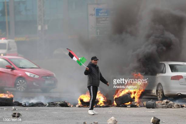 Palestinian protesters are seen as Israeli soldiers intervene in Palestinian demonstrators, gathered at Beit El military checkpoint, using tear gas...