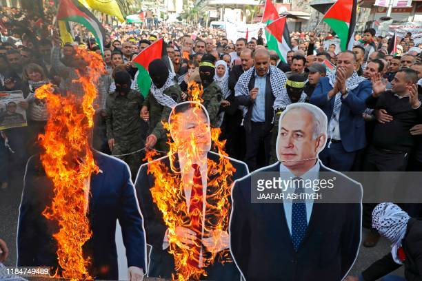 Palestinian protesters burn cardboard cutouts of US President Donald Trump, his State Secretary Mike Pompeo, and Israeli Prime Minister Benjamin...