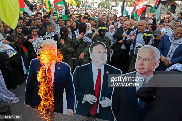 Palestinian protesters burn cardboard cutouts of US President Donald Trump his State Secretary Mike Pompeo and Israeli Prime Minister Benjamin...