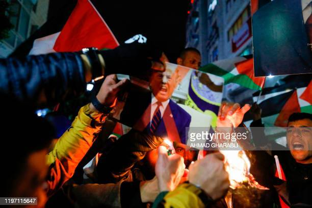 TOPSHOT Palestinian protesters burn pictures of US President Donald Trump and Israel's Prime Minister Benjamin Netanyahu during a demonstration in...