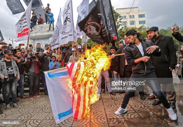 TOPSHOT Palestinian protesters burn the US and Israeli flags in Gaza City on December 6 2017 President Donald Trump is set to recognise Jerusalem as...