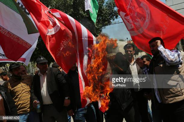 Palestinian protesters burn the US flag during a demonstration against strikes carried out by the United States Britain and France against Syria's...